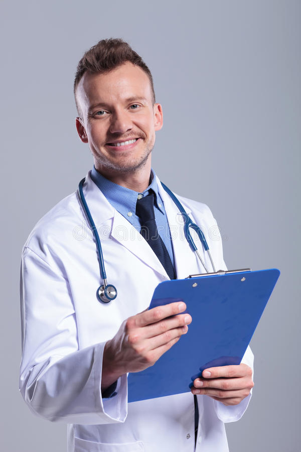 Χαμογελώντας νέος γιατρός με την περιοχή αποκομμάτων στοκ εικόνα με δικαίωμα ελεύθερης χρήσης