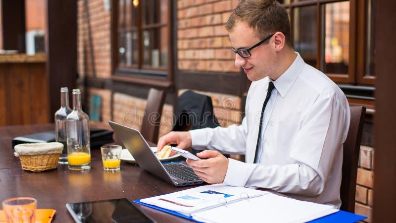 Χαμογελώντας νέος επιχειρηματίας που κάνει μια κλήση με το smartphone του σε ένα εστιατόριο. στοκ φωτογραφία με δικαίωμα ελεύθερης χρήσης