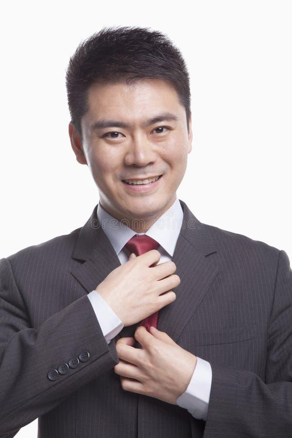 Χαμογελώντας νέος επιχειρηματίας που ρυθμίζει το δεσμό του, πυροβολισμός στούντιο στοκ εικόνα