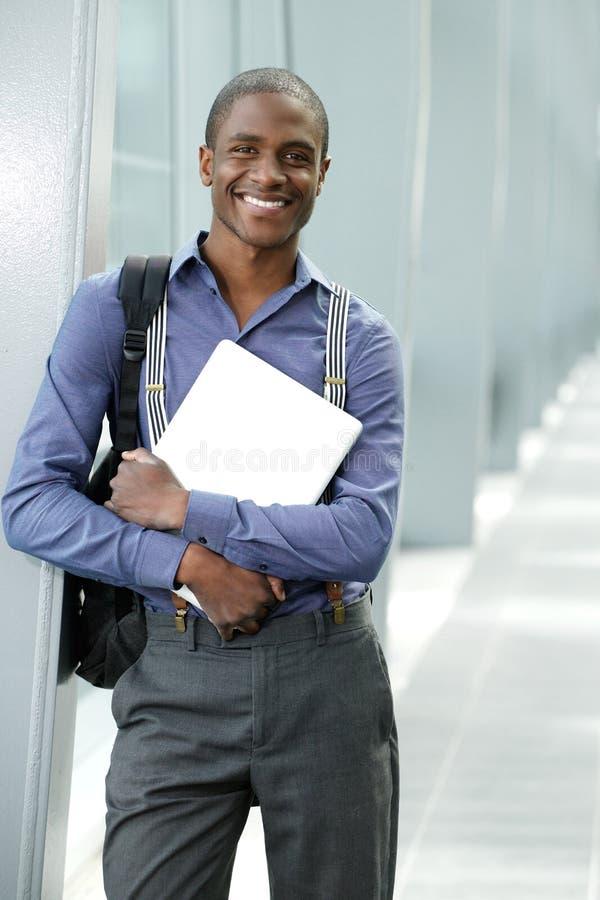 Χαμογελώντας νέος επιχειρηματίας που στέκεται στο κτήριο με το lap-top στοκ εικόνες με δικαίωμα ελεύθερης χρήσης