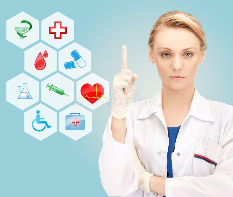 Χαμογελώντας νέος θηλυκός γιατρός που δείχνει το δάχτυλό της επάνω στοκ φωτογραφία