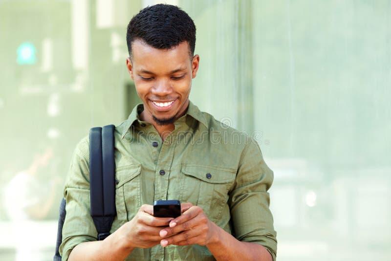 Χαμογελώντας νέος μαύρος με το έξυπνα τηλέφωνο και το σακίδιο πλάτης στοκ εικόνα με δικαίωμα ελεύθερης χρήσης