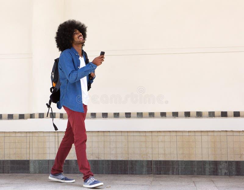 Χαμογελώντας νέος μαύρος που περπατά με την τσάντα και το κινητό τηλέφωνο στοκ φωτογραφία με δικαίωμα ελεύθερης χρήσης