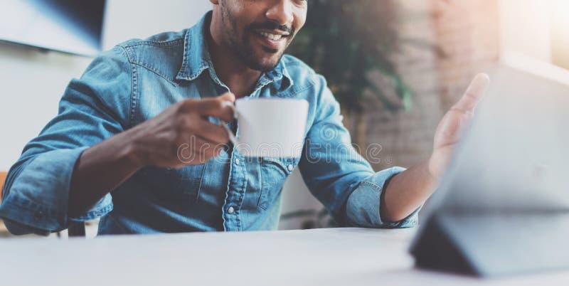 Χαμογελώντας νέο αφρικανικό άτομο που κάνει την τηλεοπτική συνομιλία μέσω της ψηφιακής ταμπλέτας με τους συνέταιρους πίνοντας το  στοκ εικόνες