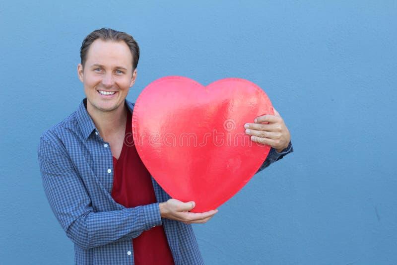 Χαμογελώντας νέο ενήλικο αρσενικό στην περιστασιακή εξάρτηση που κρατά μια μεγάλη καρδιά με τα χέρια του στοκ φωτογραφία με δικαίωμα ελεύθερης χρήσης