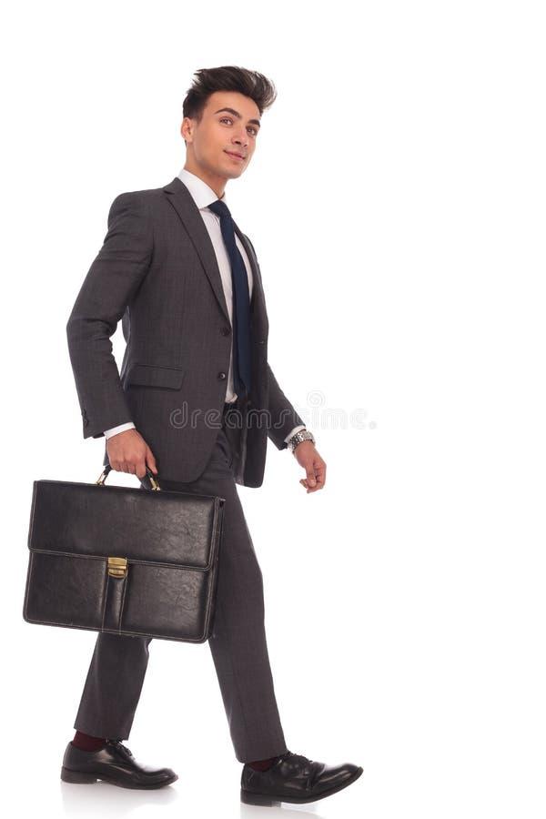 Χαμογελώντας νέο επιχειρησιακό άτομο που περπατά προς τα εμπρός και που ανατρέχει στοκ φωτογραφίες με δικαίωμα ελεύθερης χρήσης