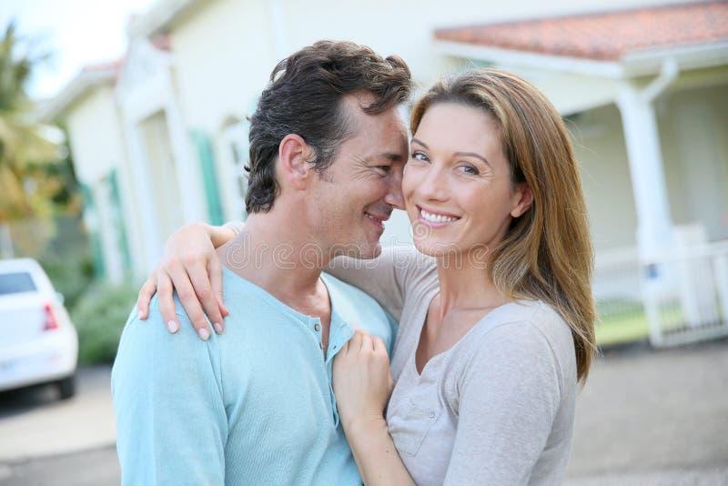 Χαμογελώντας νέο ζεύγος outisde μπροστά από το σπίτι τους στοκ φωτογραφίες με δικαίωμα ελεύθερης χρήσης