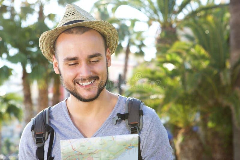 Χαμογελώντας νέο διακινούμενο άτομο που εξετάζει το χάρτη στοκ εικόνες