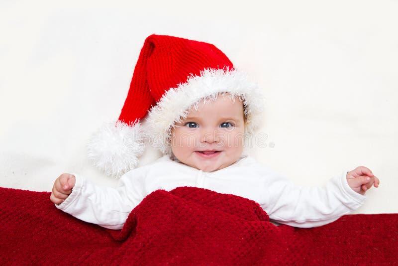 Χαμογελώντας νέο μωρό σε ένα καπέλο Άγιου Βασίλη στοκ εικόνα