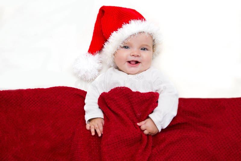 Χαμογελώντας νέο μωρό σε ένα καπέλο Άγιου Βασίλη στοκ φωτογραφία