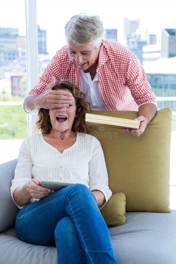 Χαμογελώντας να εκπλήξει ανδρών γυναίκα κρατώντας το δώρο στοκ εικόνα
