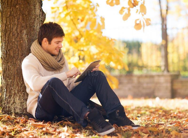Χαμογελώντας νεαρός άνδρας με το PC ταμπλετών στο πάρκο φθινοπώρου στοκ φωτογραφία με δικαίωμα ελεύθερης χρήσης
