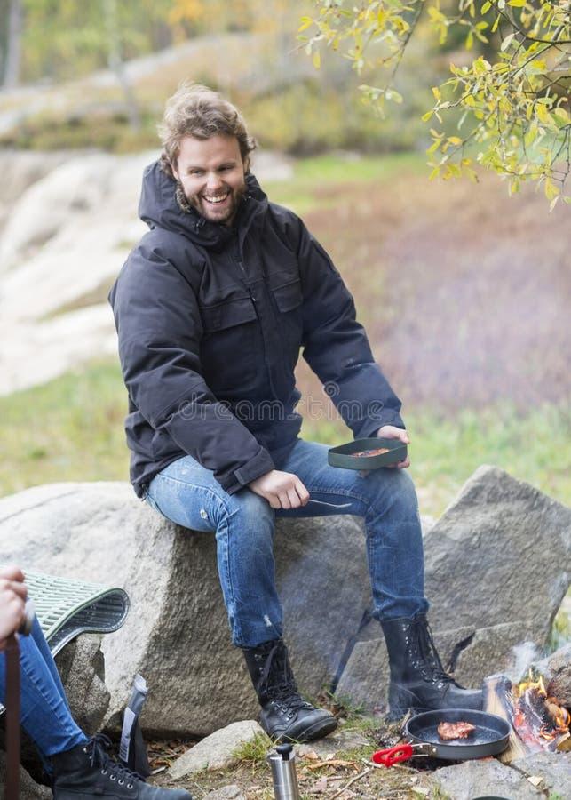Χαμογελώντας νεαρός άνδρας που έχει τα τρόφιμα στη θέση για κατασκήνωση στοκ φωτογραφία με δικαίωμα ελεύθερης χρήσης