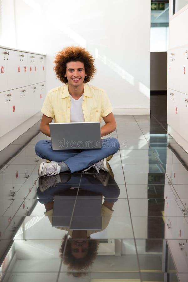 Χαμογελώντας νεαρός άνδρας που χρησιμοποιεί το lap-top στο πάτωμα στοκ φωτογραφίες