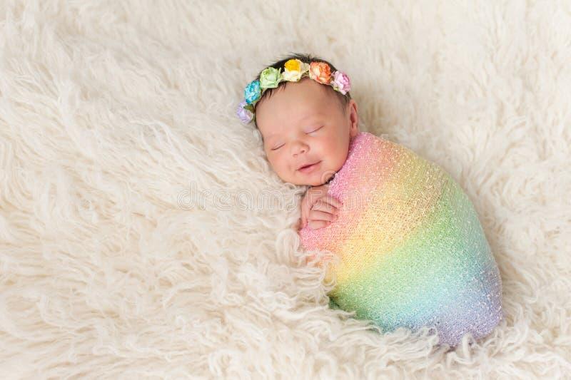 Χαμογελώντας νεογέννητο κοριτσάκι που φορά ένα χρωματισμένο ουράνιο τόξο Swaddle στοκ εικόνα με δικαίωμα ελεύθερης χρήσης