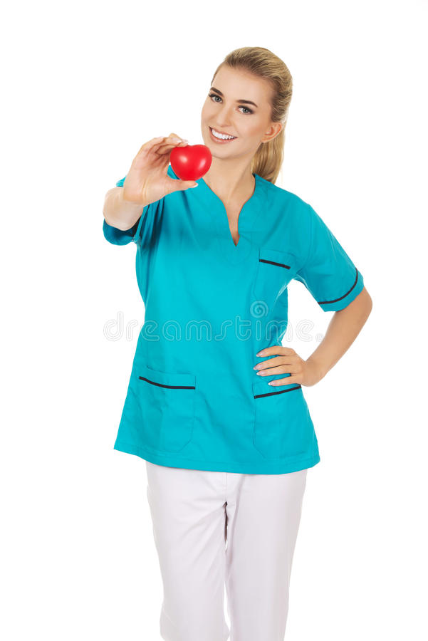Χαμογελώντας νοσοκόμα ή θηλυκός γιατρός με την καρδιά στοκ εικόνα με δικαίωμα ελεύθερης χρήσης
