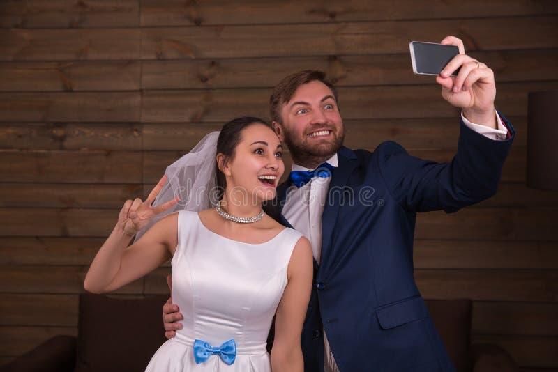 Χαμογελώντας νύφη και νεόνυμφος που κάνουν selfie στο τηλέφωνο στοκ φωτογραφίες με δικαίωμα ελεύθερης χρήσης