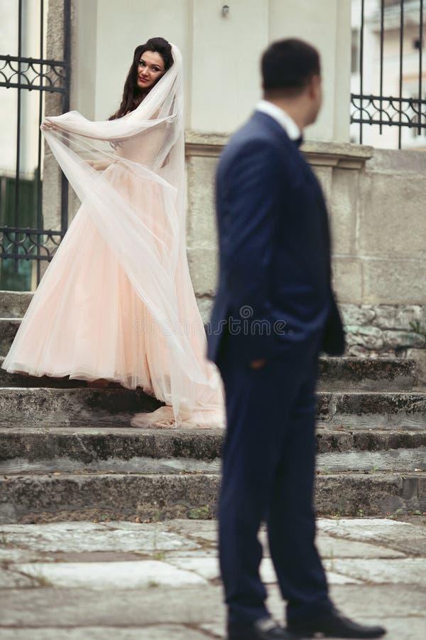 Χαμογελώντας νύφη brunette που χορεύει στα παλαιά σκαλοπάτια στον όμορφο νεόνυμφο W στοκ εικόνα