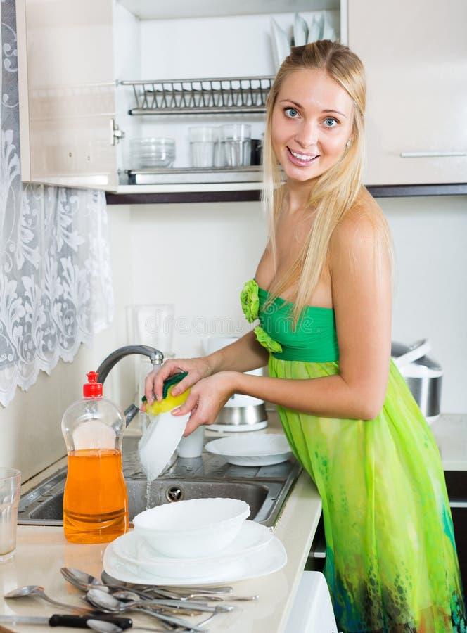 Χαμογελώντας ξανθά πιάτα πλύσης νοικοκυρών στοκ εικόνες με δικαίωμα ελεύθερης χρήσης