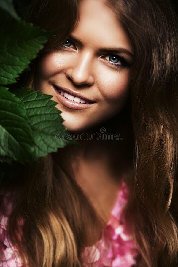Χαμογελώντας ξανθή γυναίκα πίσω από τα φύλλα στοκ φωτογραφία