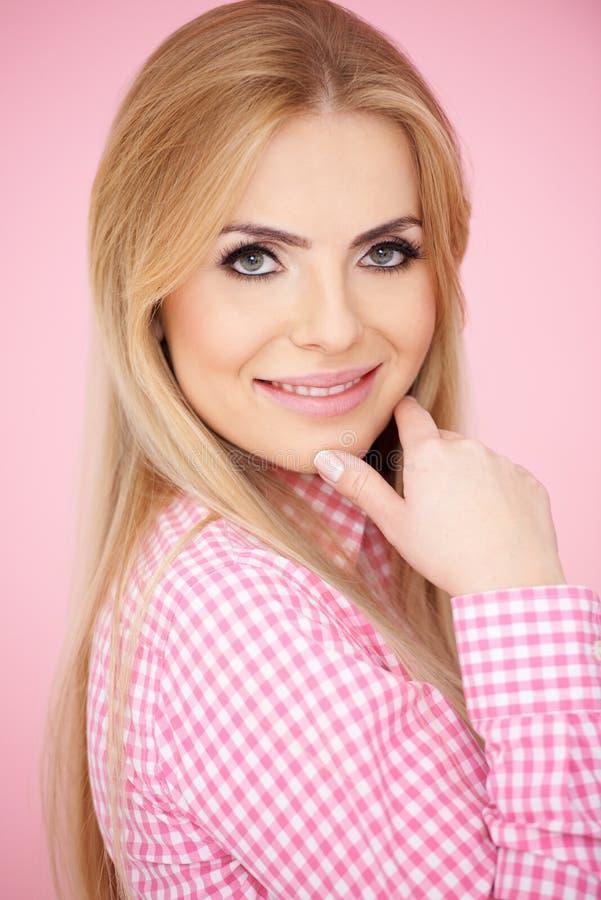 Χαμογελώντας ξανθή γυναίκα στο ρόδινο ελεγμένο πουκάμισο στοκ φωτογραφίες