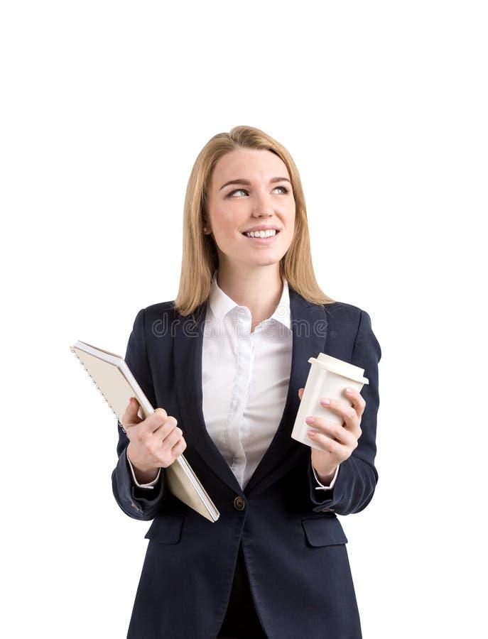 Χαμογελώντας ξανθή επιχειρηματίας με ένα σημειωματάριο και ένα φλιτζάνι του καφέ στοκ εικόνες με δικαίωμα ελεύθερης χρήσης