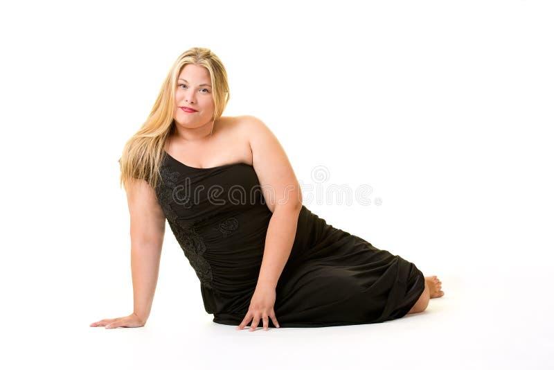 Χαμογελώντας ξανθή υπέρβαρη γυναίκα στο μαύρο φόρεμα στοκ εικόνες