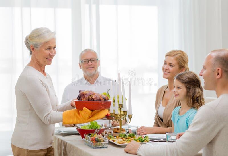 Χαμογελώντας οικογένεια που έχει το γεύμα διακοπών στο σπίτι στοκ εικόνες με δικαίωμα ελεύθερης χρήσης