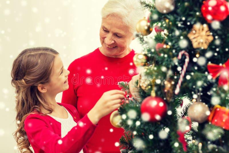 Χαμογελώντας οικογένεια που διακοσμεί το χριστουγεννιάτικο δέντρο στο σπίτι στοκ φωτογραφία με δικαίωμα ελεύθερης χρήσης