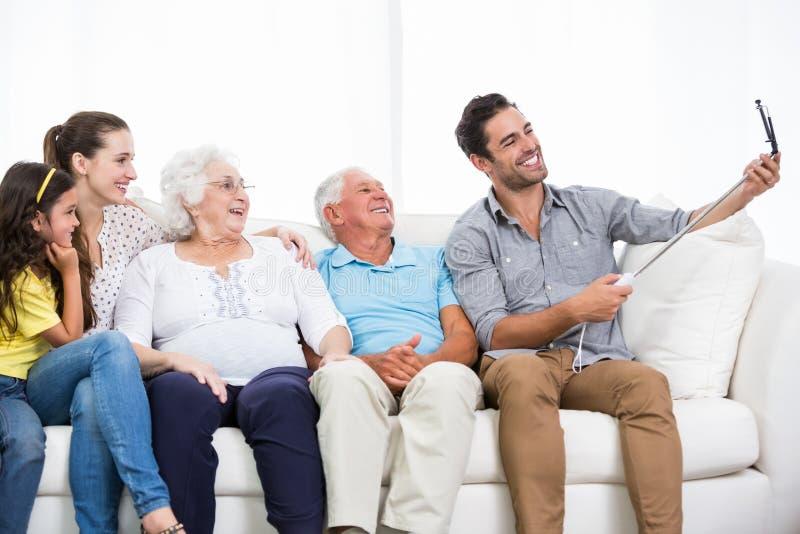 Χαμογελώντας οικογένεια που παίρνει την αυτοπροσωπογραφία καθμένος στον καναπέ στοκ φωτογραφία