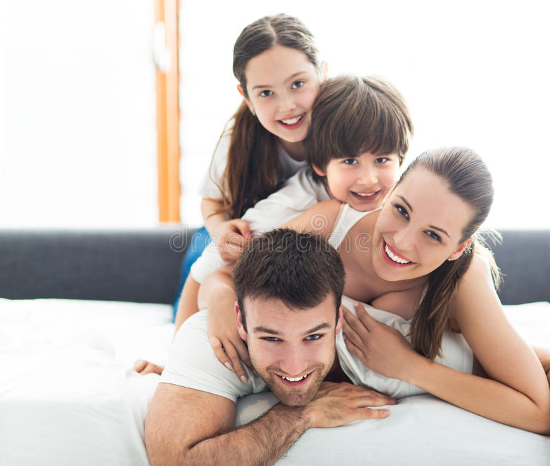 Χαμογελώντας οικογένεια στο κρεβάτι στοκ φωτογραφίες με δικαίωμα ελεύθερης χρήσης
