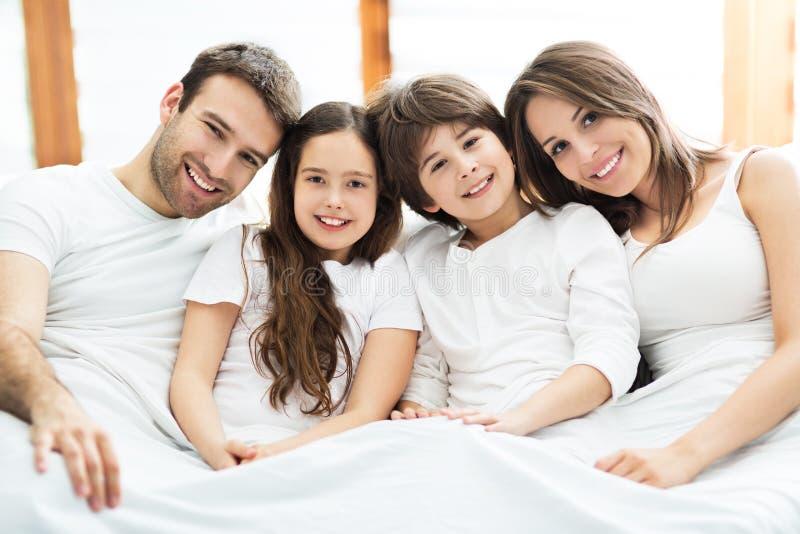Χαμογελώντας οικογένεια στο κρεβάτι στοκ φωτογραφία με δικαίωμα ελεύθερης χρήσης