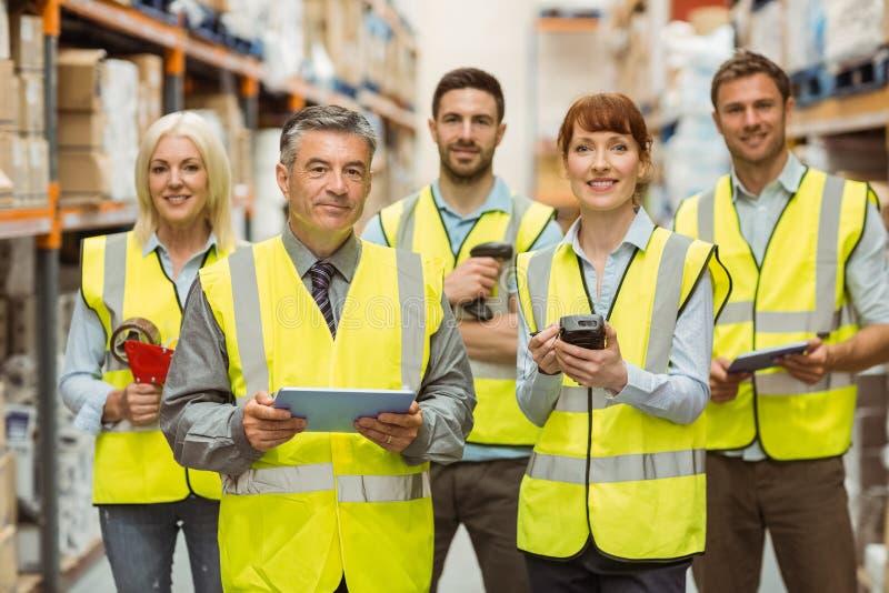 Χαμογελώντας ομάδα αποθηκών εμπορευμάτων που εξετάζει τη κάμερα στοκ εικόνα