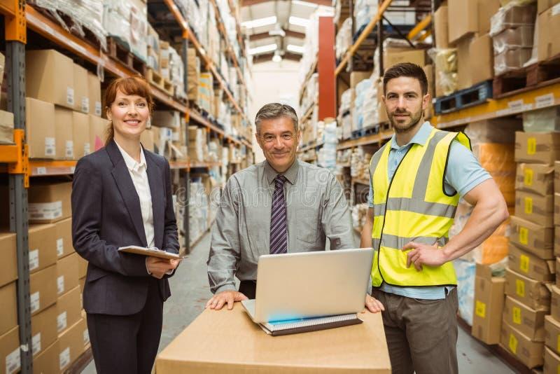 Χαμογελώντας ομάδα αποθηκών εμπορευμάτων που εργάζεται μαζί στο lap-top στοκ εικόνα με δικαίωμα ελεύθερης χρήσης