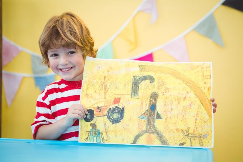 Χαμογελώντας παιδί που κρατά ψηλά την τελειωμένη ζωγραφική του στοκ φωτογραφίες με δικαίωμα ελεύθερης χρήσης