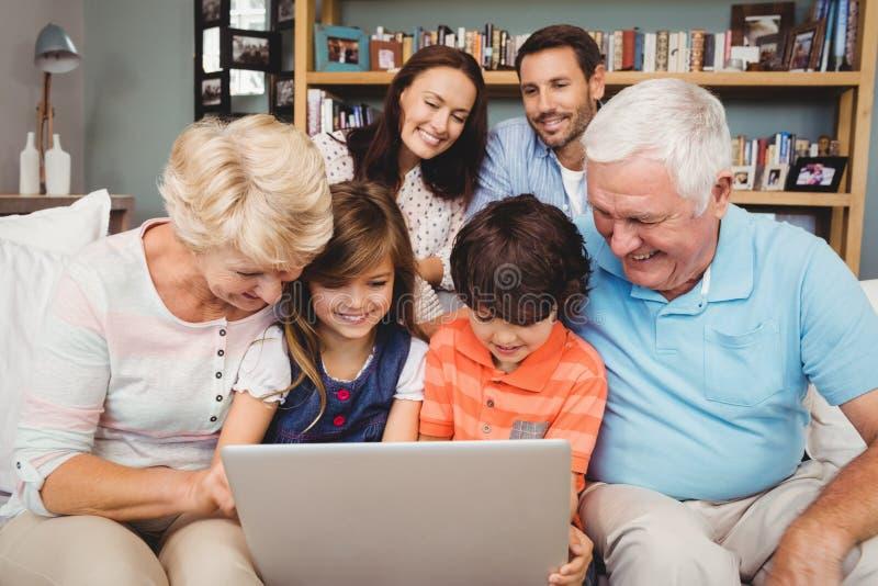 Χαμογελώντας παιδιά και παππούδες και γιαγιάδες που χρησιμοποιούν το lap-top με την οικογένεια στοκ εικόνα