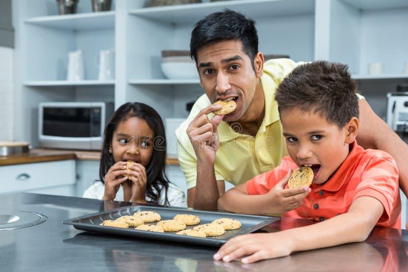 Χαμογελώντας πατέρας με τα παιδιά του που τρώνε τα μπισκότα στοκ εικόνα