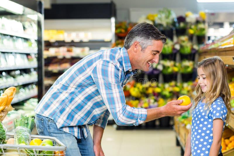 Χαμογελώντας πατέρας που δίνει ένα μήλο στη χαριτωμένη κόρη του στοκ φωτογραφίες