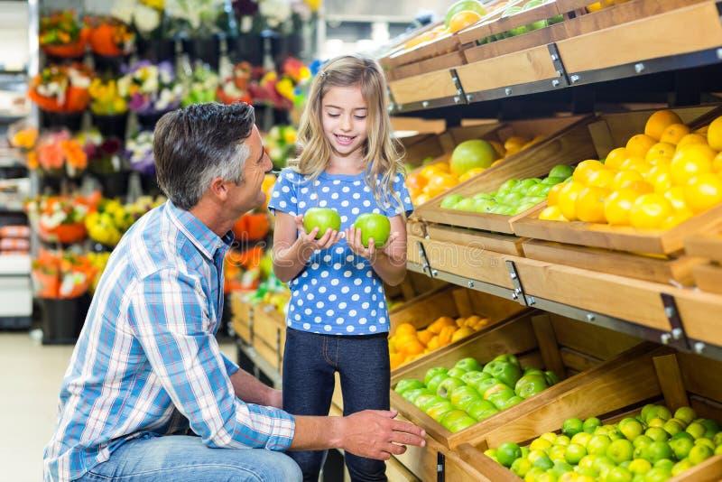 Χαμογελώντας πατέρας που δίνει τα μήλα στη χαριτωμένη κόρη του στοκ εικόνες