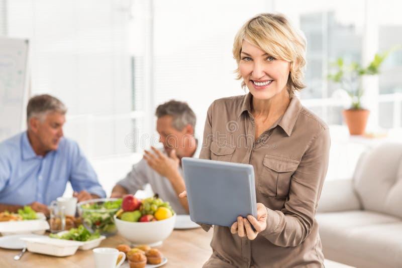 Χαμογελώντας περιστασιακή επιχειρηματίας που χρησιμοποιεί την ταμπλέτα στο μεσημεριανό γεύμα στοκ φωτογραφίες