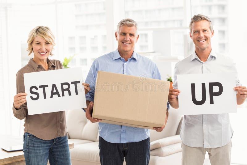 Χαμογελώντας περιστασιακοί επιχειρηματίες που κρατούν το σημάδι ξεκινήματος στοκ φωτογραφία με δικαίωμα ελεύθερης χρήσης