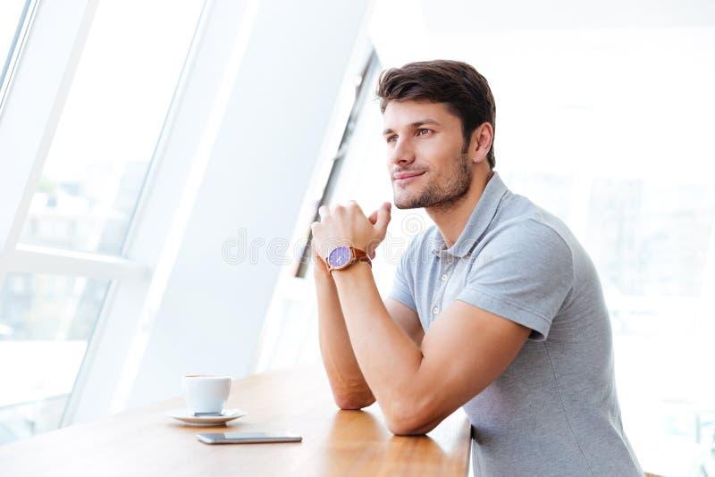 Χαμογελώντας περιστασιακός νεαρός άνδρας που έχει το διάλειμμα στον καφέ στοκ εικόνες
