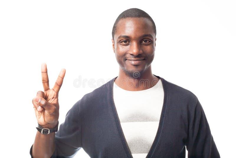 Χαμογελώντας περιστασιακός ντυμένος μαύρος που παρουσιάζει σημάδι ειρήνης στοκ φωτογραφία