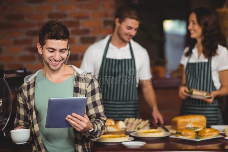 Χαμογελώντας πελάτης που εξετάζει την ταμπλέτα στοκ εικόνα με δικαίωμα ελεύθερης χρήσης