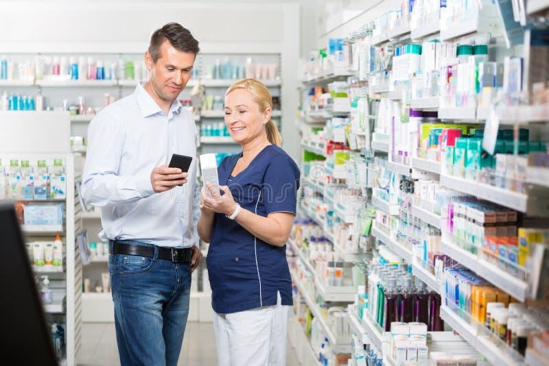 Χαμογελώντας πελάτης που παρουσιάζει πληροφορίες προϊόντων για το κινητό τηλέφωνο στοκ εικόνες