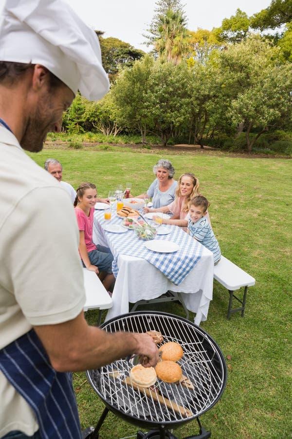 Χαμογελώντας πολυμελής οικογένεια που έχει μια σχάρα που μαγειρεύεται από τον πατέρα στοκ εικόνα με δικαίωμα ελεύθερης χρήσης