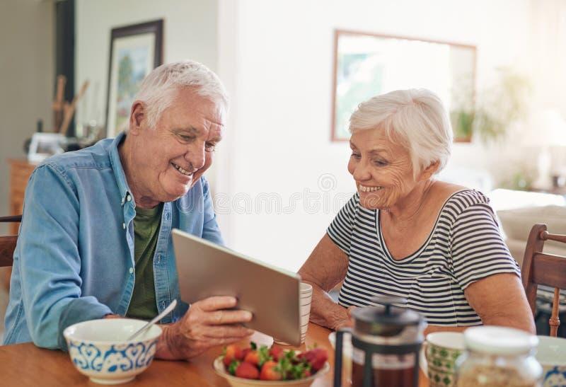 Χαμογελώντας πρεσβύτεροι που χρησιμοποιούν μια ψηφιακή ταμπλέτα μαζί πέρα από το πρόγευμα στοκ εικόνα με δικαίωμα ελεύθερης χρήσης