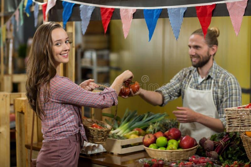 Χαμογελώντας προμηθευτής που δίνει τις ντομάτες στη γυναίκα στο μετρητή στο μανάβικο στοκ φωτογραφία