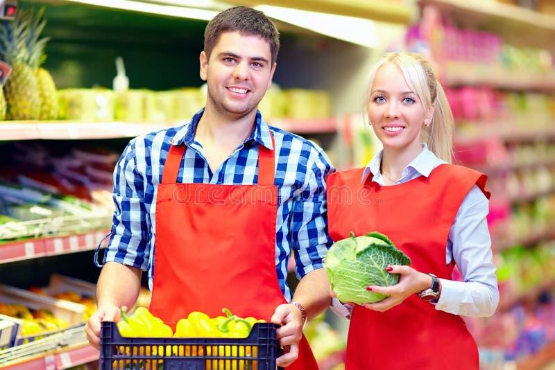 Χαμογελώντας προσωπικό παντοπωλείων που εργάζεται στην υπεραγορά στοκ φωτογραφίες με δικαίωμα ελεύθερης χρήσης