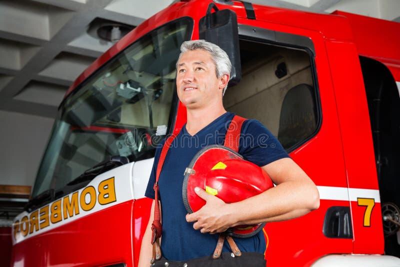 Χαμογελώντας πυροσβέστης που κοιτάζει μακριά ενώ κόκκινο εκμετάλλευσης στοκ φωτογραφία με δικαίωμα ελεύθερης χρήσης